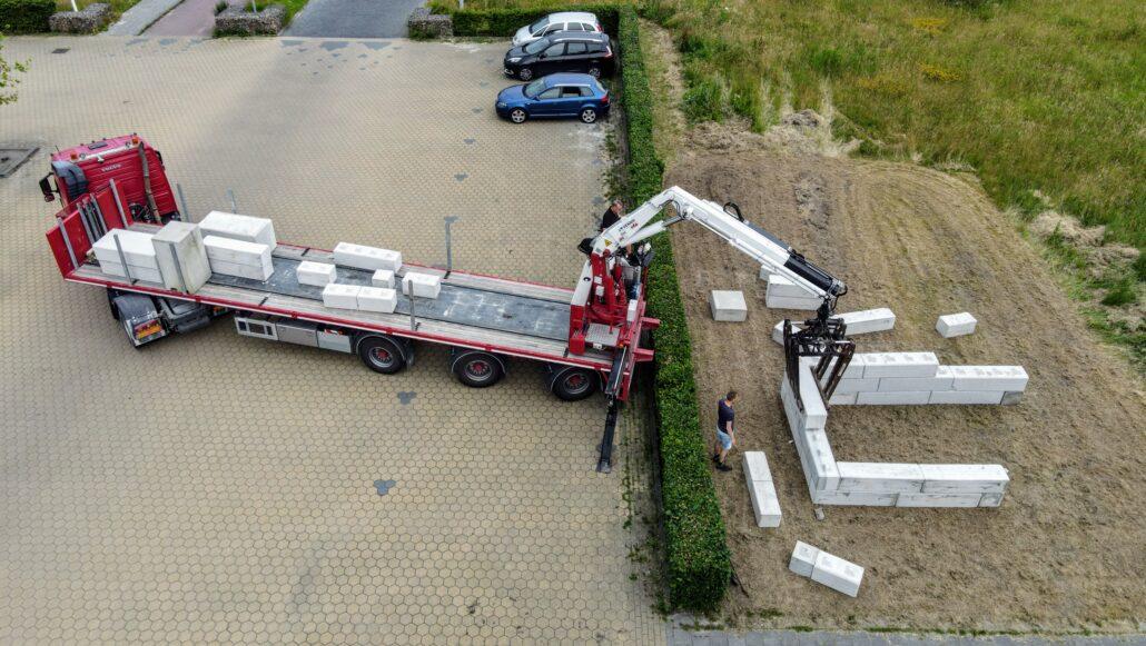 Installatie van betonblokken voor proefopstelling freerunnen.